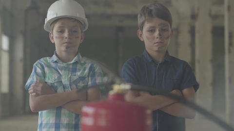 Two little boys with dirty faces and in protective helmets looking at the fire Live Action