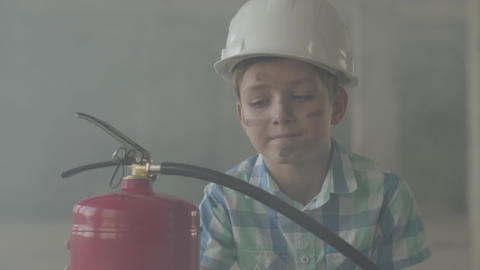 Portrait of a small boy in a white protective helmet with a fire extinguisher Footage