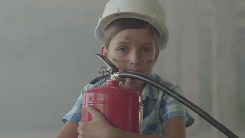 Portrait of a little boy in a white protective helmet with a fire extinguisher Live Action