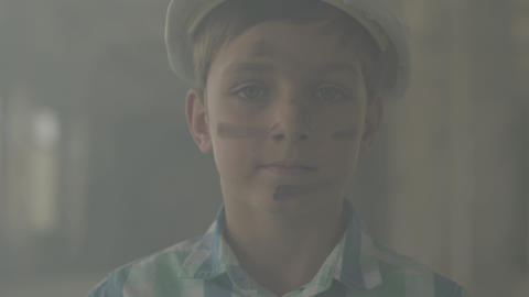Portrait teen boy in a protective helmet looking at the camera in the background Live Action