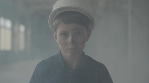 Portrait of boy in a protective helmet coming out of a pillar of smoke and Live Action