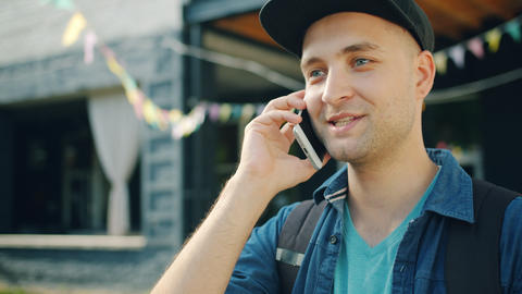 Portrait of handsome student talking on mobile phone outside in the street Footage