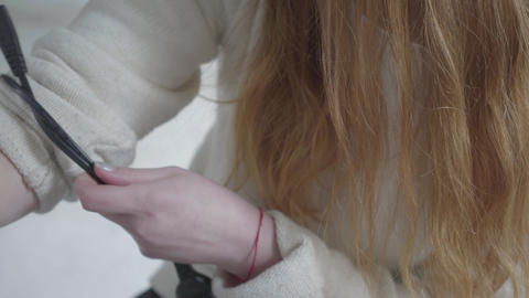 Young red-haired junkie girl is tying a cord on her arm for blood rush to vein Footage