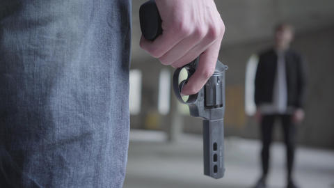 Male hand holding the revolver in hand close-up. The guy puts and removes finger Footage