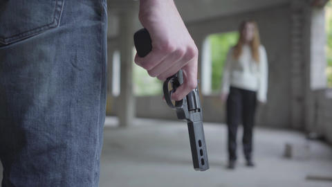 Close-up of male hand holding the revolver in hand. A nervous young man going to Footage