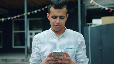 Portrait of handsome mixed race man using smartphone touching screen outside Footage
