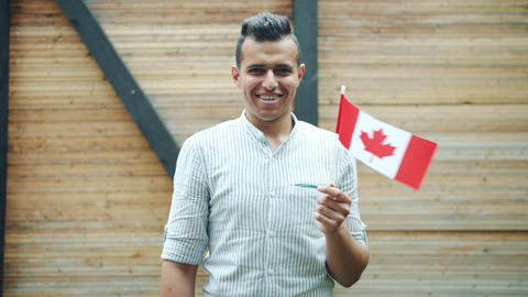 Portrait of attractive mixed race man holding Canadian flag smiling outdoors Live Action