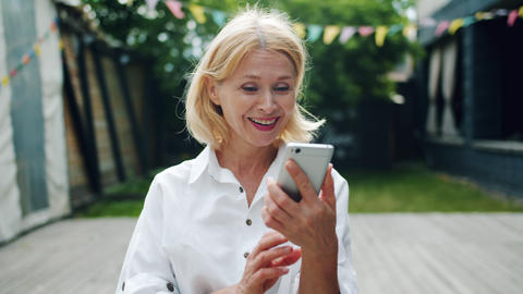 Happy mature lady taking smartphone looking at screen laughing enjoying content Live Action