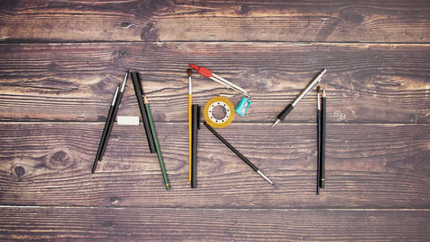 Art word written with art and drawing supplies on wooden background - Stop motion Animation