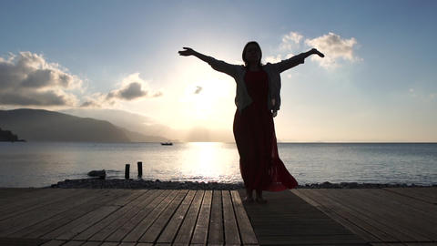 Adult woman doing spiritual practice near the sea at sunrise in slow motion Live Action