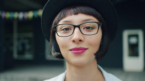 Close-up portrait of young pretty girl in glasses and hat smiling outdoors Live Action