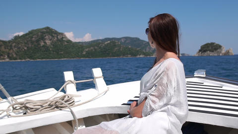 A girl in glasses is on the bow of the boat, enjoying the beautiful scenery Live Action