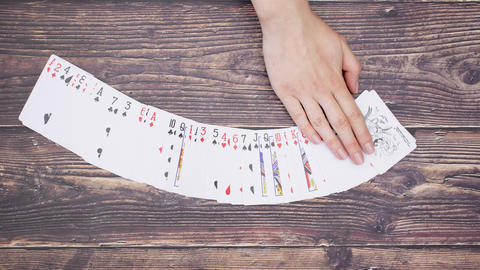 Woman's hand move deck of cards on wooden background - Stop motion Animation