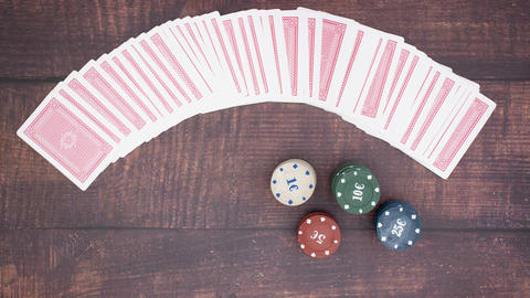 Deck of cards moving and poker chips on wooden background - Stop motion Animation