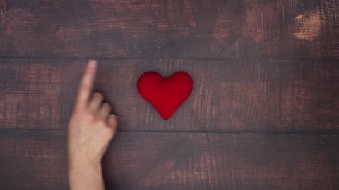 Woman's hand move red heart from wooden background - Stop motion Animation