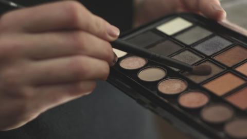 Woman hold a palette of eye shadows and second hand smears the shadows Footage