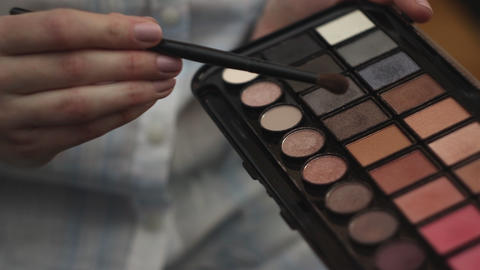 Woman hold a palette of eye shadows and smears the shadows Footage