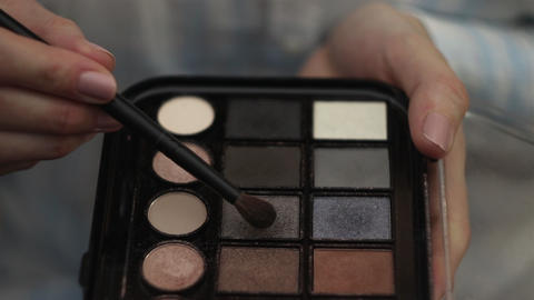 Woman hold a palette of eye shadows and with other hand smears the shadows Footage