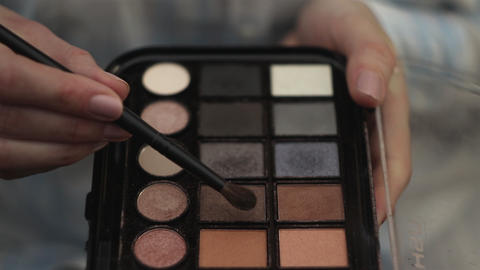 Woman hold a palette of eye shadows and with second hand smear the shadows Footage