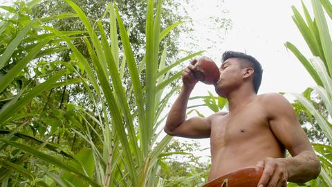 Indigenous Man Drinking Sugarcane Juice In The Amazon Rainforest Footage