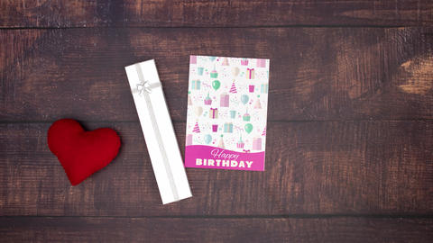 Birthday card and present appear on on wooden background and red heart pass by - Stop motion Videos animados
