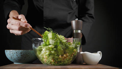 Man mixes vegetarian green salad with the wooden spoon on the dark background Footage