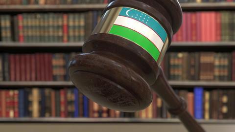 Flag of Uzbekistan on falling judges gavel in court. National justice or Live Action