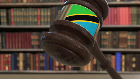 Flag of Tanzania on falling judges gavel in court. National justice or Live Action