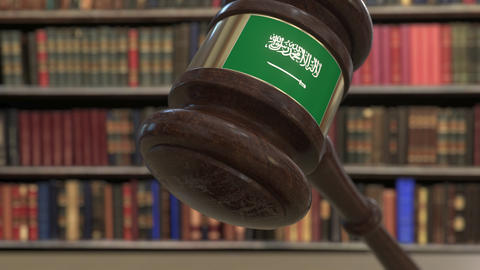 Flag of Saudi Arabia on falling judges gavel in court. National justice or Live Action