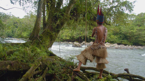 Indigenous Man Swinging On A Rope Over A River In The Amazon Rainforest Footage