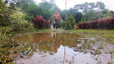 Indigenous Kid Throwing Himself Into A Puddle In An Amazon Village Live Action