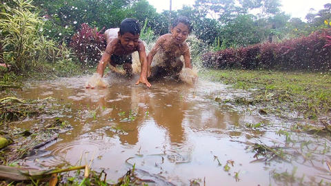 Indigenous Kids Throwing themselves Into A Puddle In An Amazon Village Live Action