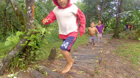 Indigenous Family Running Through A Log Path In A Amazon Village Live Action