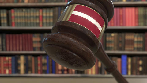 Flag of Latvia on falling judges gavel in court. National justice or Live Action