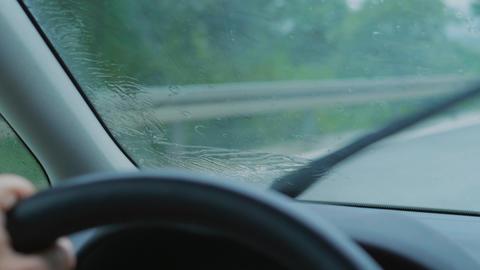 Rain drops on driving car front window, rain-sensing wipers Acción en vivo