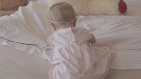 Little baby girl in a diaper playing alone on the bed at home. Lovely child in Footage