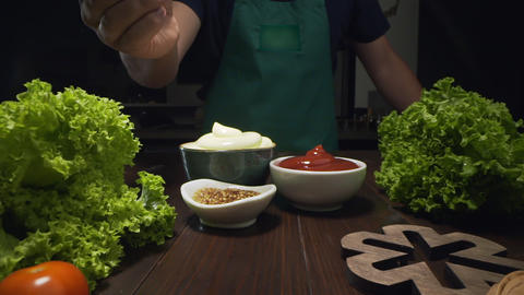 Slider zooming shot: chef cooking vegetables and takes mustard with spoon Live Action