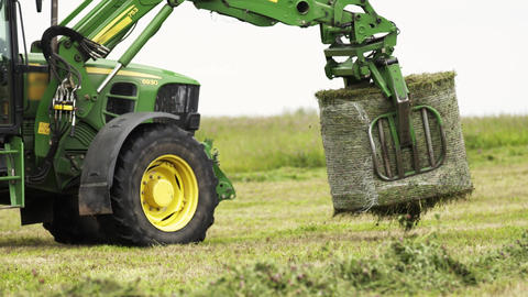 Green tractor picks up stack of grass with metal claw at farm field Live Action