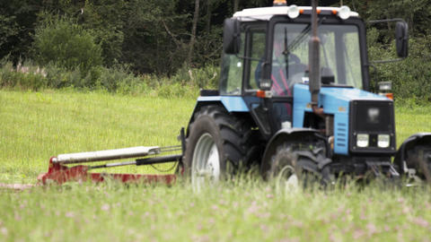 Blue tractor riding cutting grass field at farm near forest Live Action