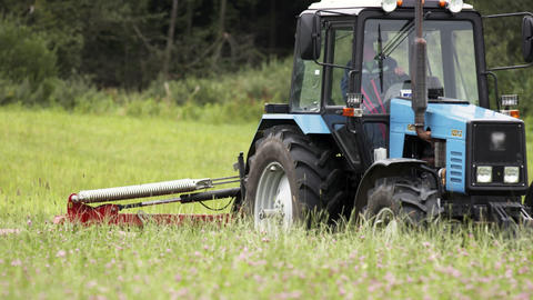 Blue tractor riding cutting grass margin at farm near forest Live Action