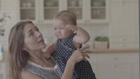 Close-up portrait of a beautiful mom and cute baby indoors together. Caucasian Footage