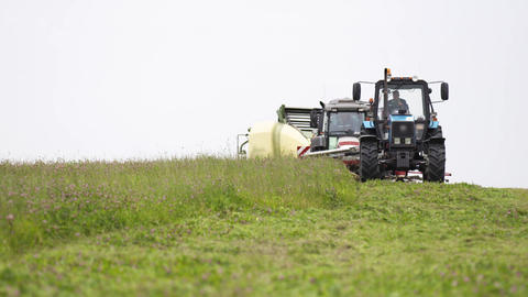 Line of agriculture machines riding on grass field at farm Live Action