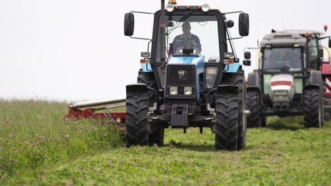 Line of agriculture tractors driving on grass margin at farm Live Action