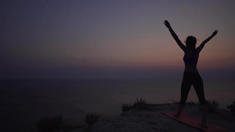 Silhouette of a slender young woman practicing yoga at sunset, raises her arms Footage