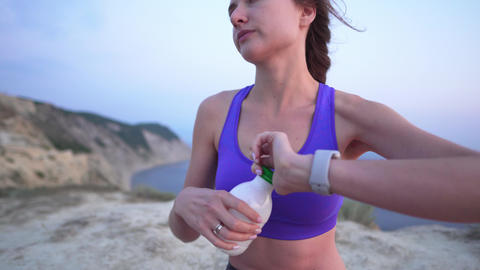 Attractive beautiful woman drinks protein after sports training. Young sports Live Action