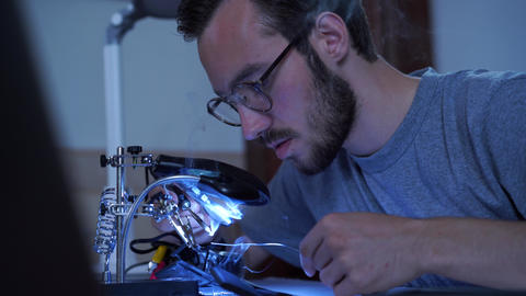 Portrait of skill young bearded man in glasses working with a soldering iron at Live Action