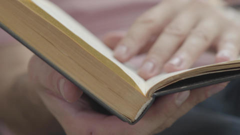 Close-up of male hands leafing through the pages of the book indoors. Concept of Footage