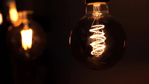 The lamps lights up in the dark. Tungsten light bulb lamps over black background Live Action
