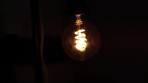 Tungsten light bulb lamp over black background. Concept of light and dark, idea Footage