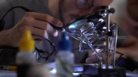 Young bearded apprentice in glasses working with soldering iron at his working Footage